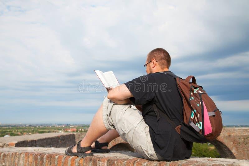 坐户外读的年轻人 库存图片