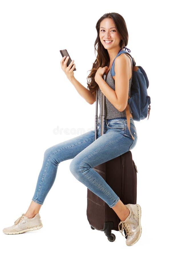 坐手提箱和拿着手机的年轻女性亚裔旅客的充分的身旁反对被隔绝的白色背景 库存照片