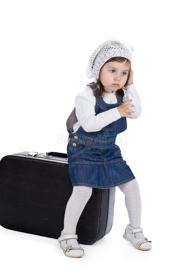坐手提箱女孩由电话叫 库存照片