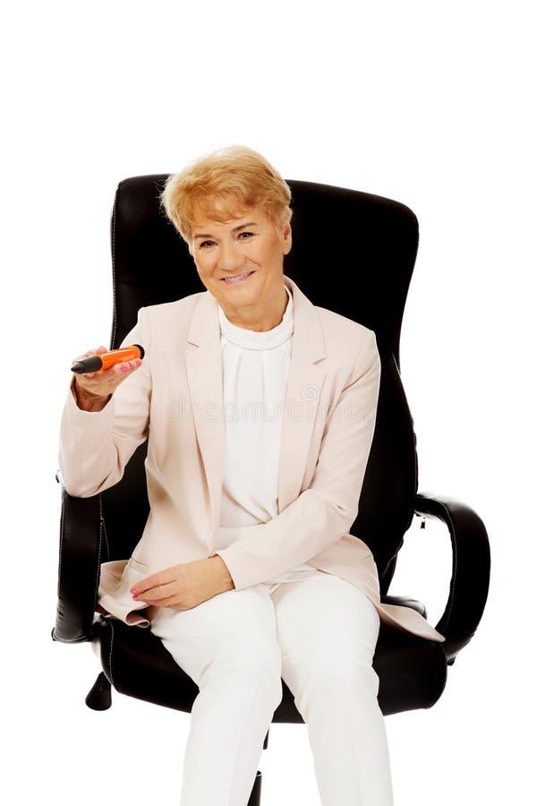 坐扶手椅子和拿着巨大的笔的微笑年长女商人 免版税库存照片