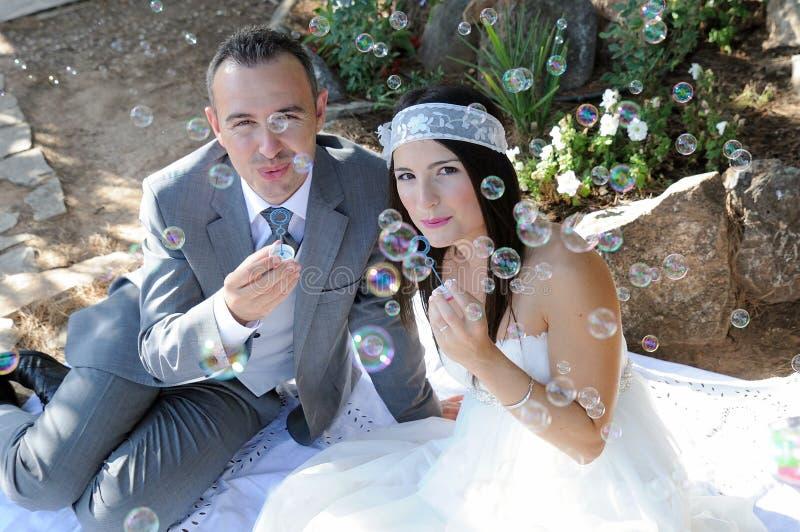 坐新郎的新娘做室外的肥皂泡 免版税库存照片