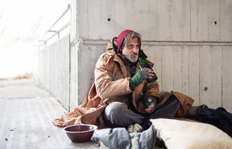 坐无家可归的叫化子的人一张正面图户外,拿着瓶酒精 复制空间 库存照片