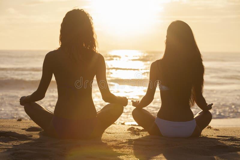 坐日出日落比基尼泳装海滩的妇女女孩 免版税库存照片
