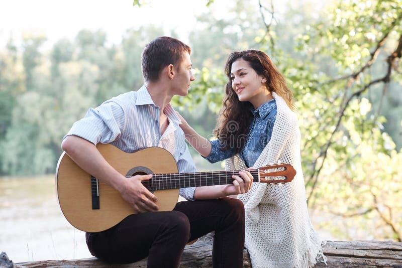 坐日志由河和演奏吉他、夏天自然、明亮的阳光、阴影和绿色叶子的年轻夫妇,浪漫 免版税库存图片