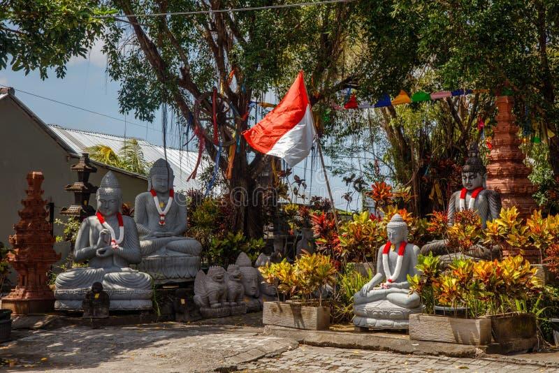 坐有有诗歌选的菩萨石雕象在印度尼西亚旗子的红色和白色颜色印度尼西亚的美国独立日 图库摄影