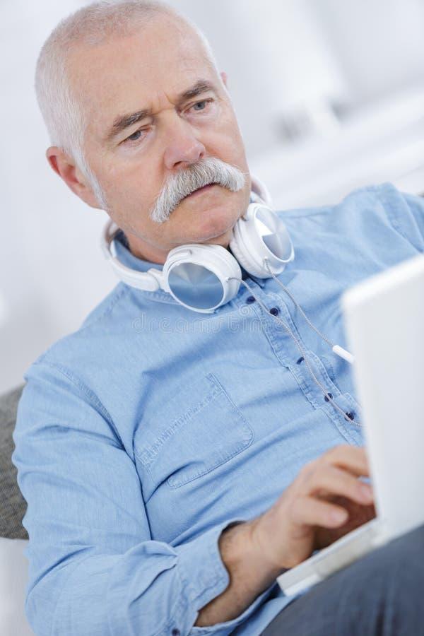 坐有耳机的沙发和使用膝上型计算机的老人 免版税库存照片