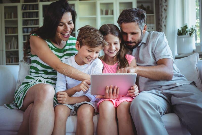 坐有他们的孩子的沙发和使用数字式片剂的父母在客厅 库存图片