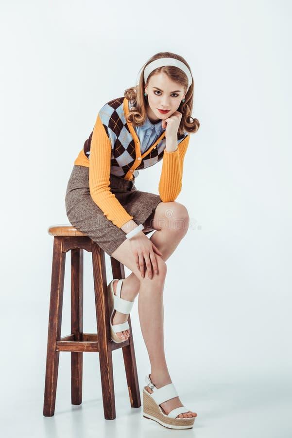 坐木椅子和看照相机的美丽的减速火箭的被称呼的女孩 免版税库存照片