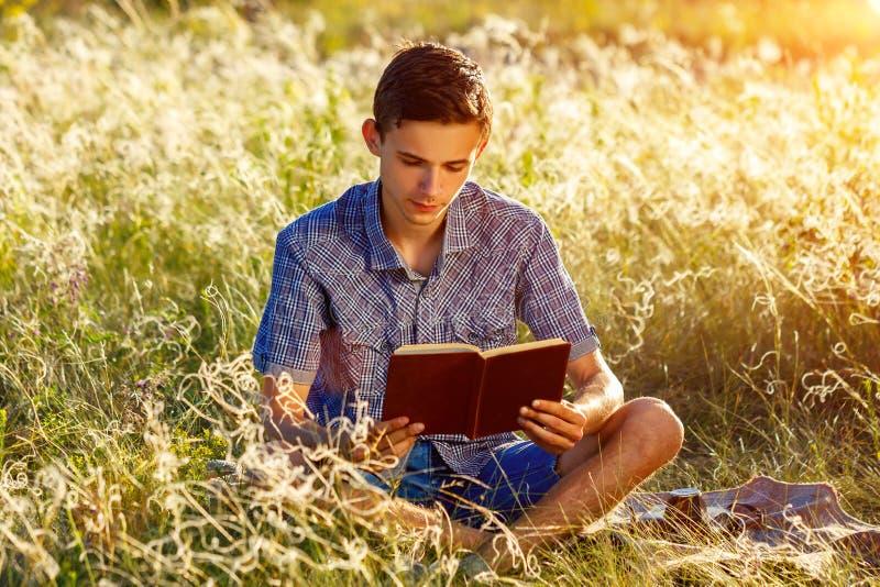 坐本质上的年轻人读书 库存图片