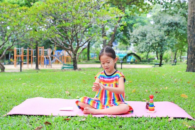 坐桃红色床垫和应用润肤液的可爱的矮小的亚裔儿童女孩在夏天庭院里 库存照片