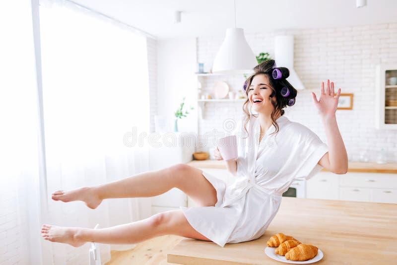 坐桌和摆在照相机的年轻正面管家 大声笑  波浪用手 在板材的新月形面包 免版税库存照片