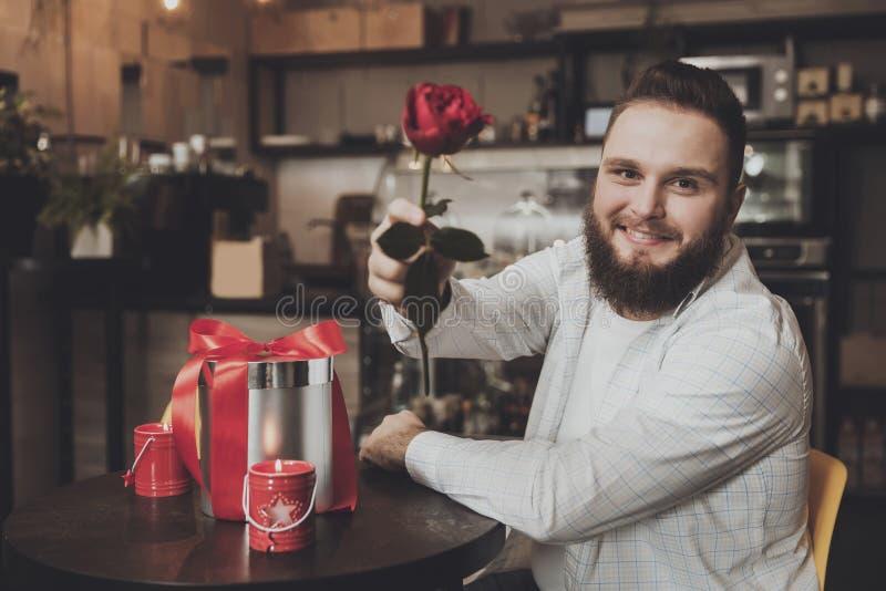 坐桌的微笑的年轻人拿着玫瑰 免版税库存照片