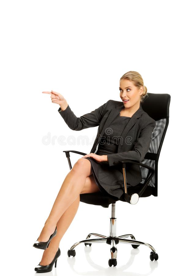 坐椅子和显示空的空间的女实业家 图库摄影