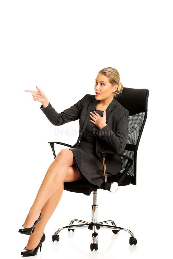 坐椅子和显示空的空间的女实业家 免版税库存图片