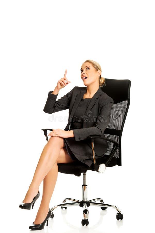 坐椅子和显示空的空间的女实业家 库存照片