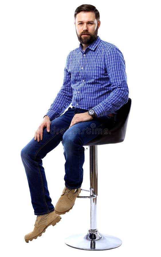 坐椅子和看照相机的骄傲和满意的年轻人被隔绝在白色 库存图片