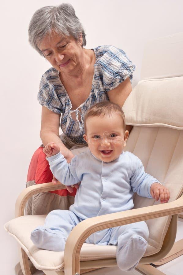 坐椅子和笑与祖母的婴孩 免版税库存图片