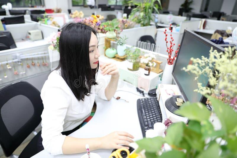 坐椅子认为在工作便携式计算机微笑穿戴企业职业衣服工作场所的亚洲中国办公室夫人妇女女孩 图库摄影