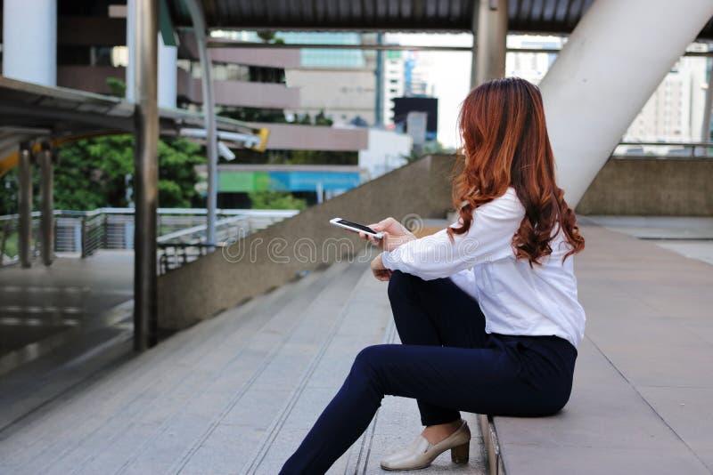 坐楼梯和在她的手上的孤独的亚裔妇女侧视图拿着流动巧妙的电话 库存照片