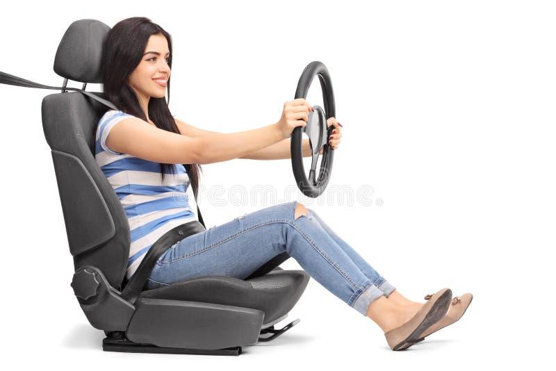 坐汽车座位和拿着轮子的妇女 库存照片