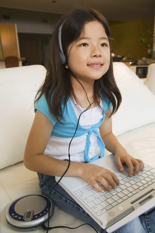 坐沙发使用膝上型计算机和听到音乐的女孩 免版税库存照片
