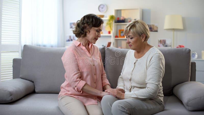 坐沙发和举行手、健康问题、支持和关心的翻倒妇女 免版税库存照片