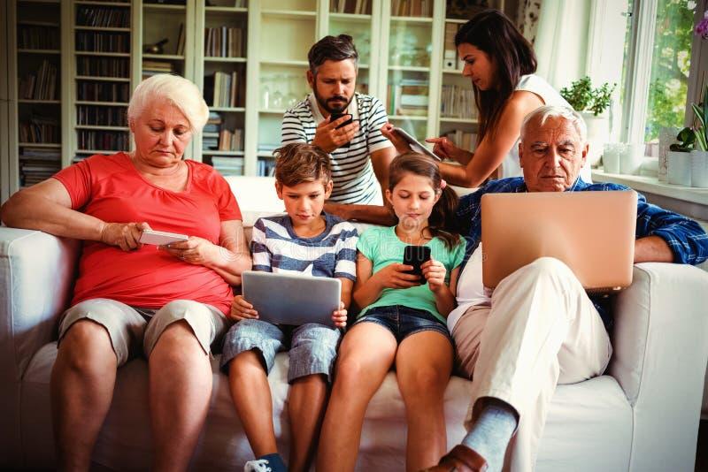 坐沙发和使用各种各样的技术的多代的家庭 免版税库存照片