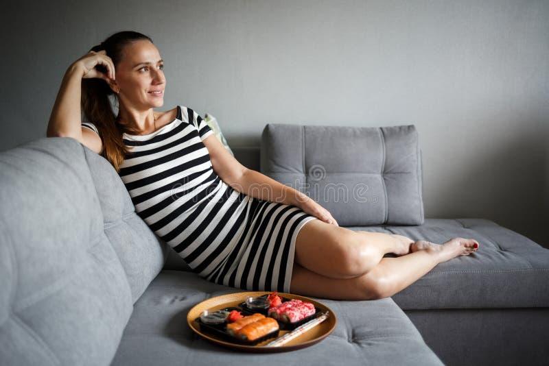 坐沙发和吃寿司的年轻可爱的妇女 库存图片