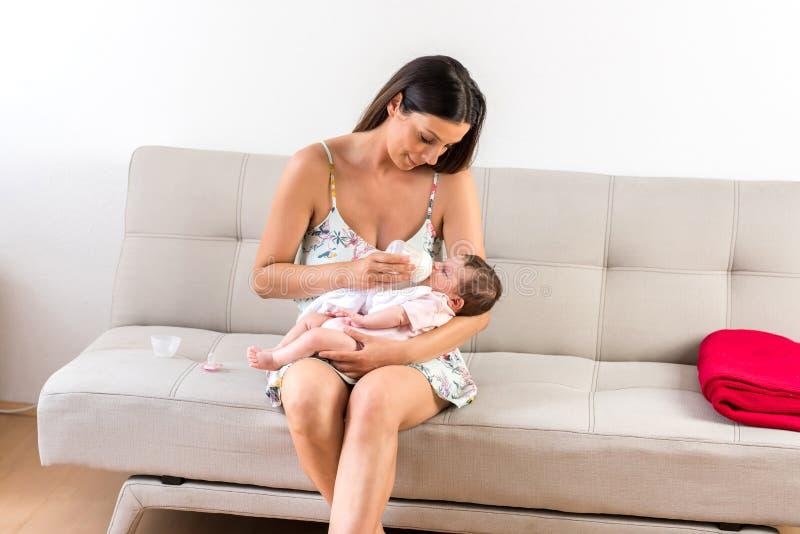 坐沙发和喂养她的婴孩的一个年轻母亲 库存照片