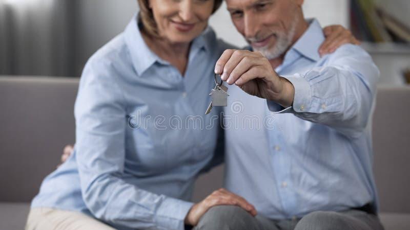 坐沙发和拿着家型钥匙圈,不动产的年迈的夫妇 免版税图库摄影
