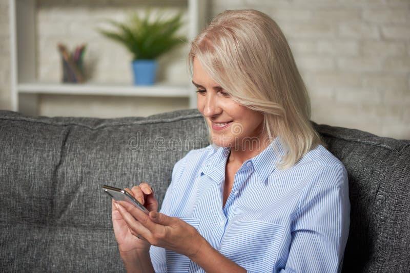 坐沙发和拿着智能手机的资深微笑的妇女 库存图片