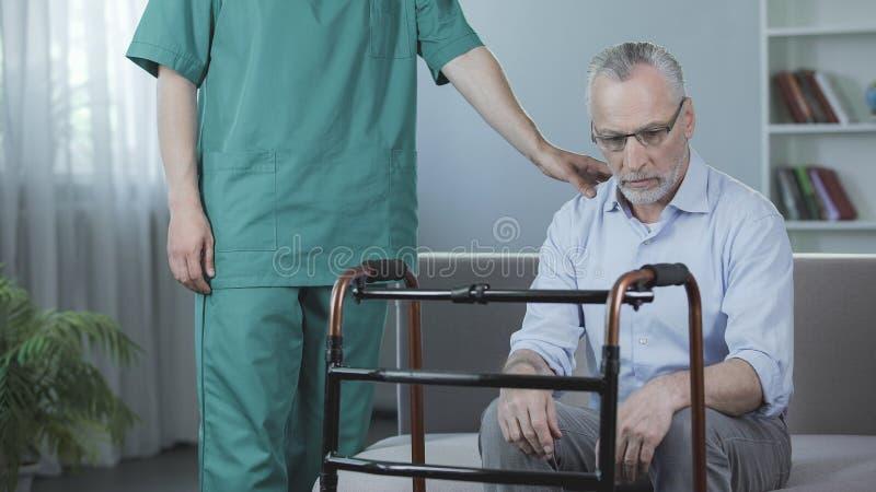 坐沙发和看充满悲伤的不适的资深男性走的框架 免版税图库摄影