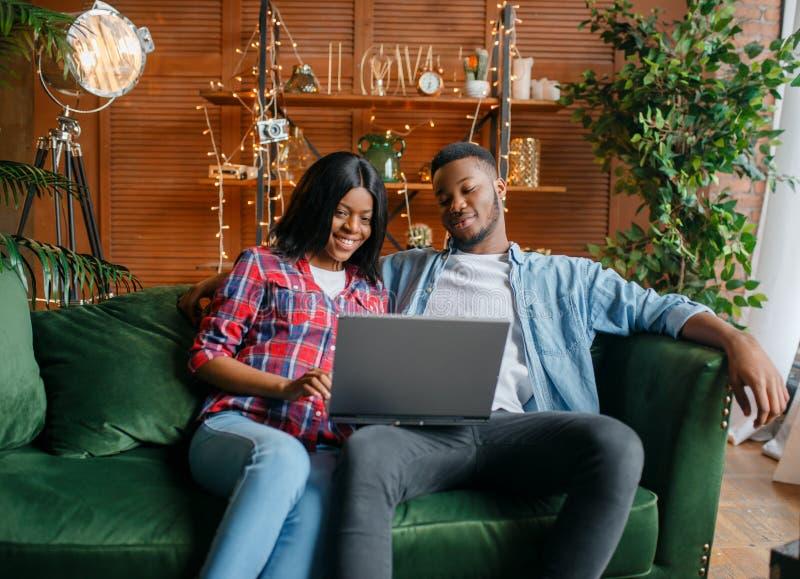 坐沙发和看在膝上型计算机的黑夫妇 免版税库存照片