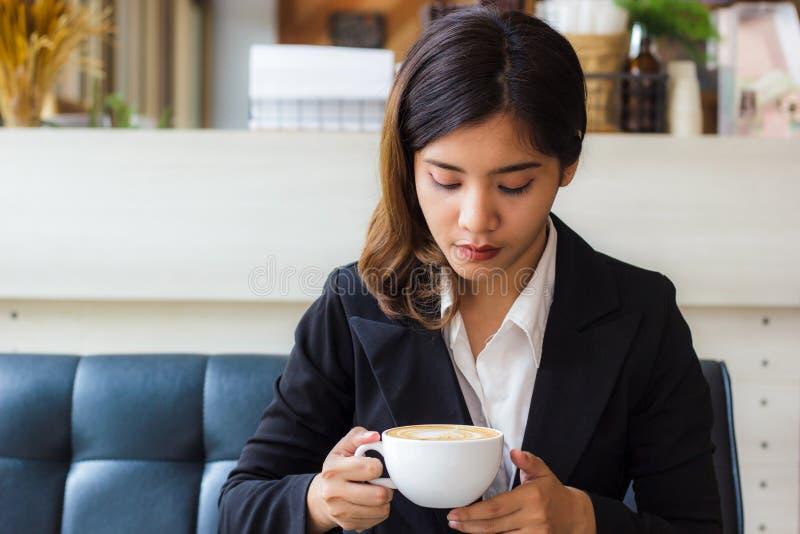 坐沙发和看杯子热的咖啡的一个美丽的亚裔女商人在她的手上 库存图片