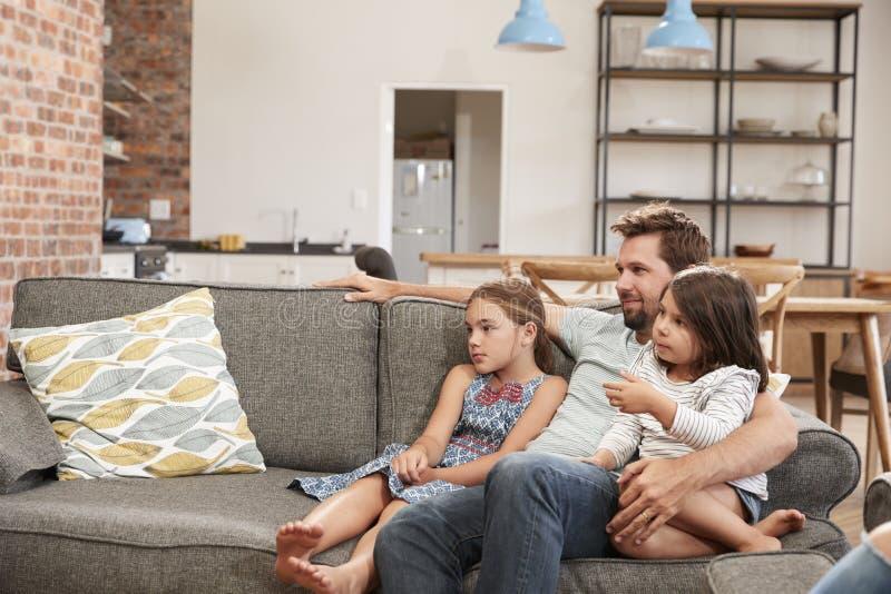 坐沙发在休息室看电视的父亲和孩子 库存照片
