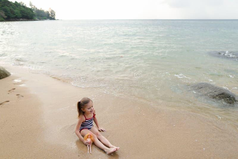 坐沙子在海附近和使用与玩偶的小女孩 免版税库存图片