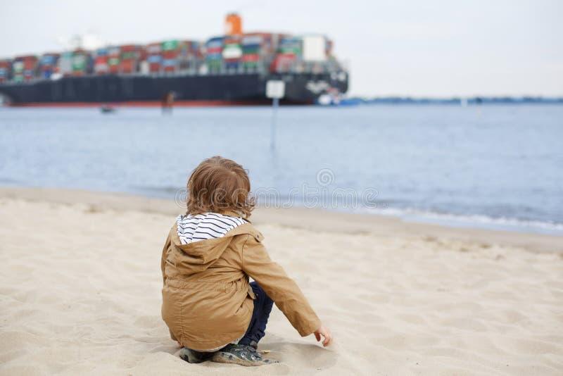 坐沙子海滩和看在containe的小小孩男孩 免版税库存图片