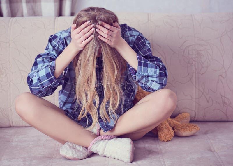 坐沮丧的少年拿着头在手上,其次是玩具熊 有被注重的哀伤的年轻女人精神 免版税库存图片