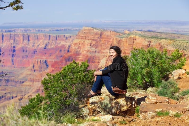 坐沿岩石壁架的两种人种的青少年的女孩在大峡谷 库存图片