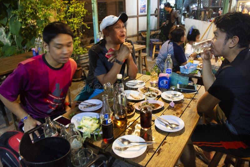 坐泰国人朋友的人民吃食物和喝啤酒在地方餐馆在暖武里,泰国 免版税图库摄影