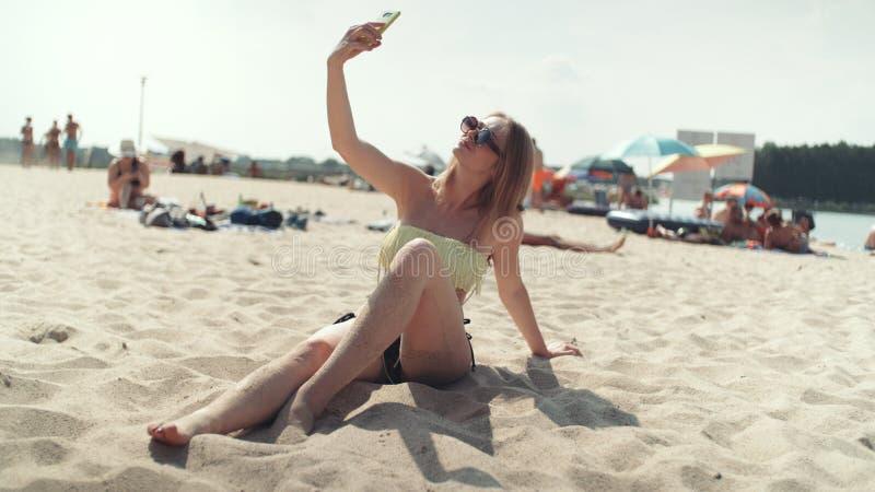 坐海滩和采取selfie的比基尼泳装的俏丽的妇女 免版税库存照片