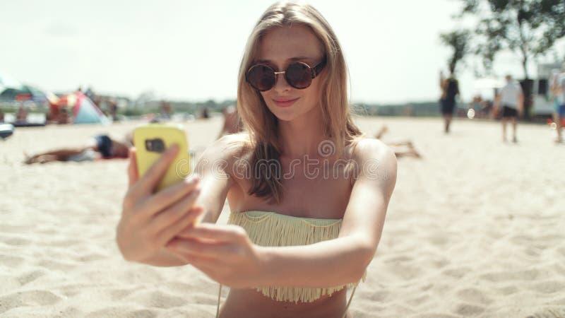 坐海滩和采取selfie的比基尼泳装的俏丽的妇女 免版税库存图片