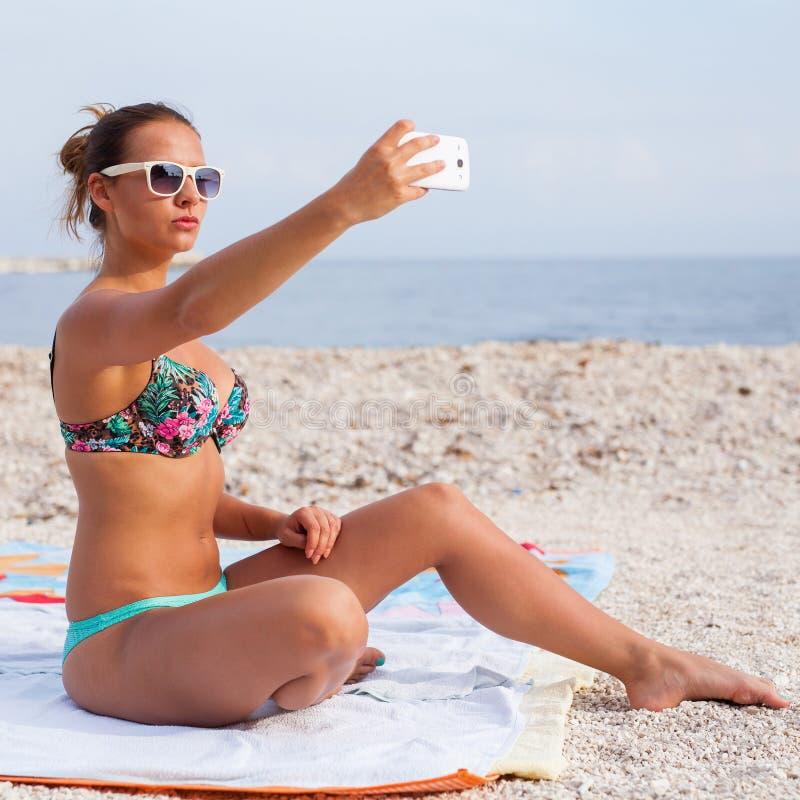 坐海滩和采取selfie的俏丽的女孩由她的电话 免版税图库摄影
