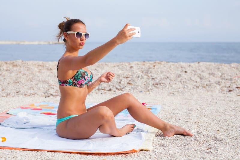 坐海滩和采取selfie的俏丽的女孩由她的电话 库存图片
