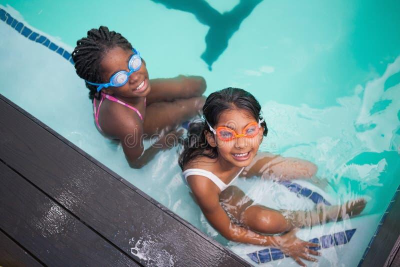 坐游泳池边的逗人喜爱的小孩 免版税库存图片