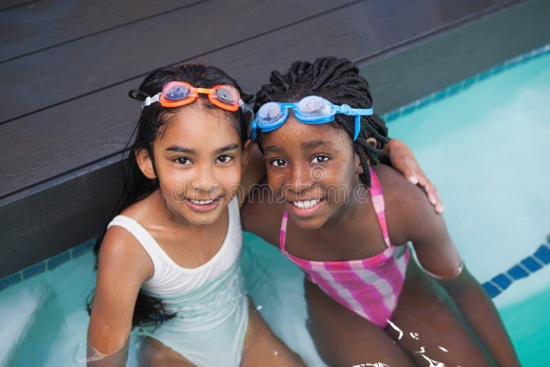 坐游泳池边的逗人喜爱的小孩 库存照片
