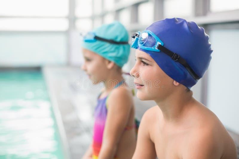 坐游泳池边的逗人喜爱的矮小的兄弟姐妹 免版税图库摄影