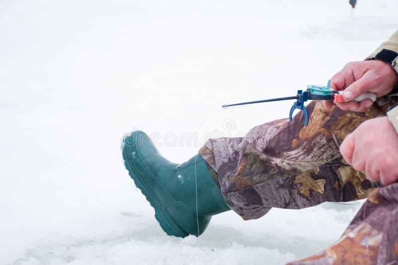 坐湖或河的冰冷的表面和拿着冰渔的渔夫一根短的冬天钓鱼竿 从w的一个场面 图库摄影