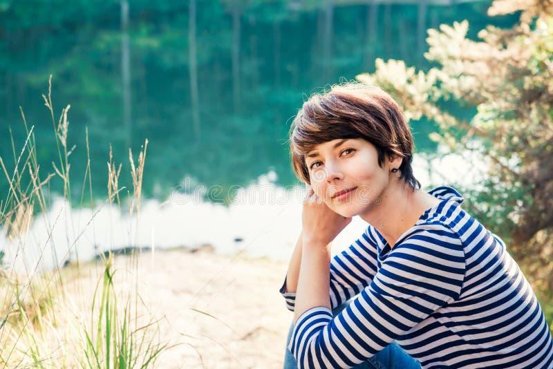 坐湖边和享受美好的平静的天的梦想的妇女接近的画象注视着湖和森林田园诗安静 免版税库存图片