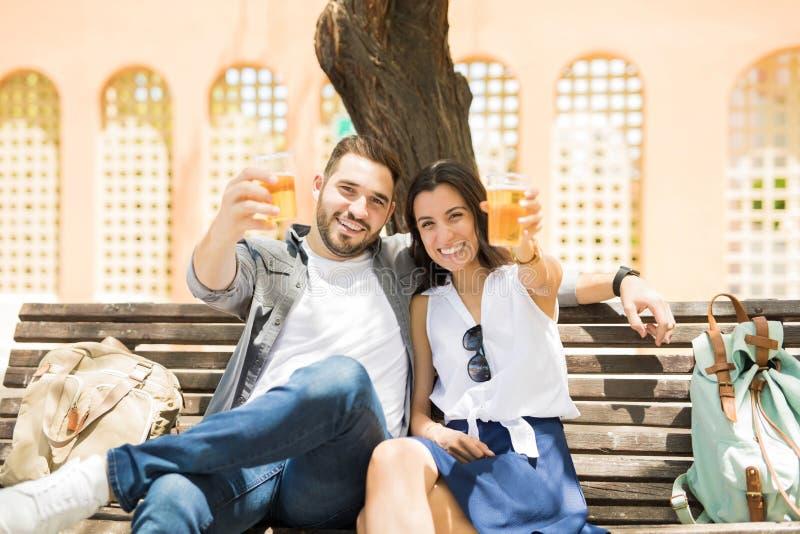 坐激动的夫妇培养往照相机的饮料 库存图片
